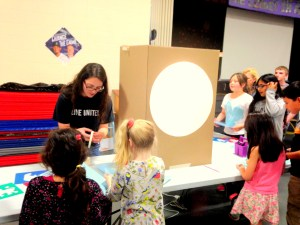 Jessica Adams, Westgate Art Docent, teaches students how to make a shadow puppet.