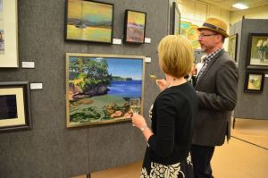 Patrons admire some of the hundreds of works on display at The Frances Anderson Center gym.