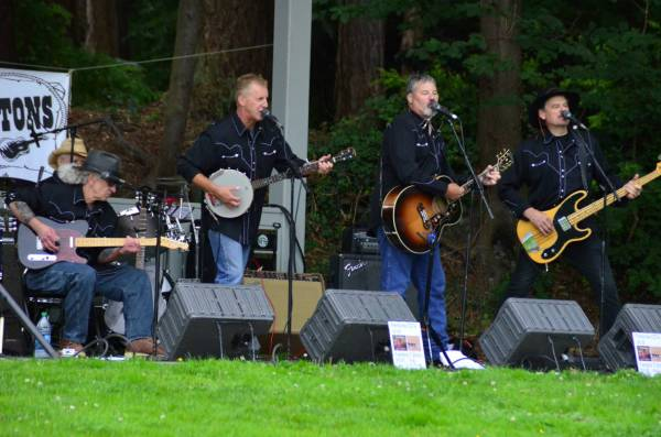 The Fentons get their twang on under cloudy skies at Edmonds City Park in the third offering of this summer's Sunday Concerts in the Park, presented by the Edmonds Arts Commission and sponsored by the Hazel Miller Foundation, Lynnwood Honda and Acura of Lynnwood. The concert ended just in the nick of time before the skies opened up for a late- afternoon rain shower. (Photo by Larry Vogel)
