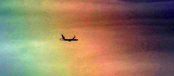 "I was photographing birds at the marsh Saturday evening with my large telephoto lens. A brief shower produced a rainbow in the eastern sky as an airplane heading towards SeaTac flew past. The rainbow did not show up well in my original photos.  I used a post processing feature called ""autocontrast"", which turned the photos  into a psychedelic flight of fancy."