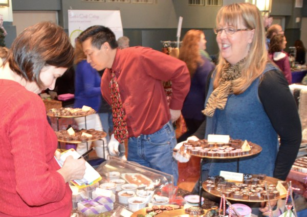 A shopper writes a check at a popular booth featuring fine chocolates.