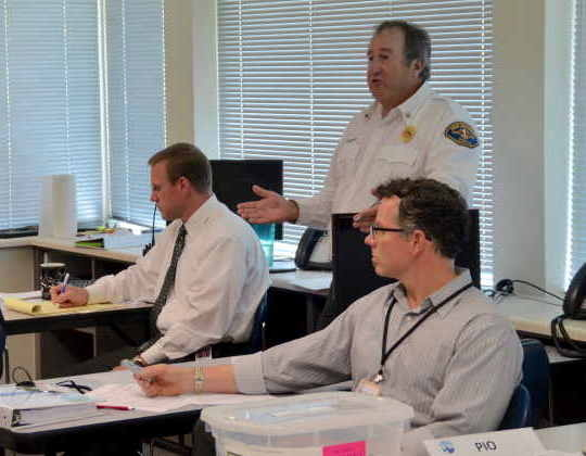 Fire District 1 Interim Chief Brad Reading, standing, talks about logistical issues. Others in photo, from left, are Assistant Police Chief Don Anderson and City Clerk Scott Passey.