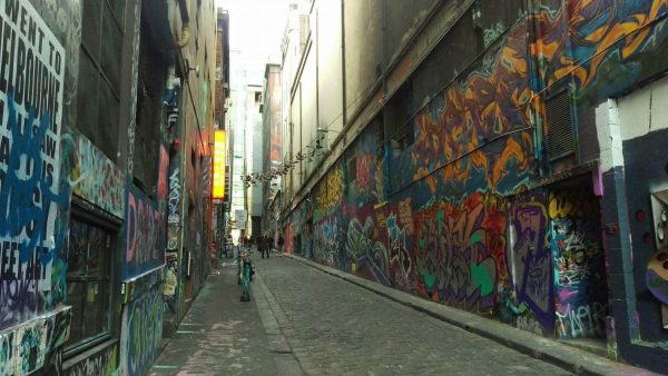 Graffiti art covers an alley between two tall buildings.