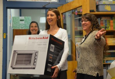 Inspirus Credit Union's Morgan Cole (center) and Marit Ernst (left) delivers a convection oven to Mrs. Caesar's (right) class.