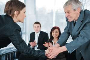 Young business woman passed on a job interview shaking hands with boss