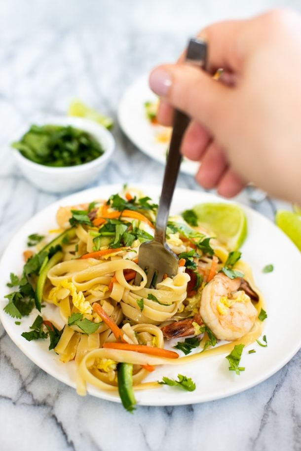 plate of shrimp noodle stir fry with fork in it