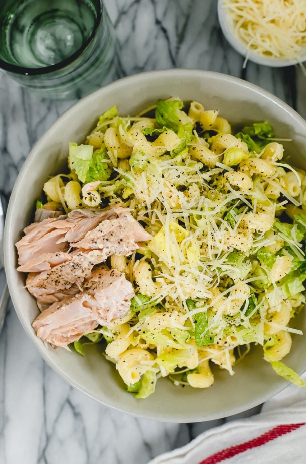 Caesar pasta salad in serving bowl with salmon