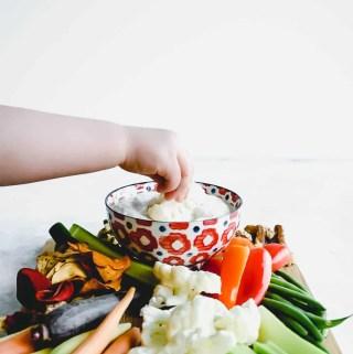 hand dipping into greek yogurt veggie dip