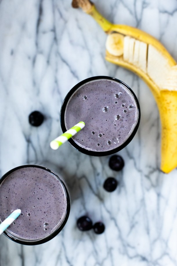 glass of blueberry banana smoothie with straw