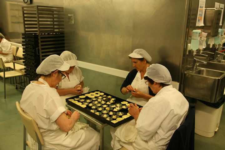 Hand pressing of pastries into the mould
