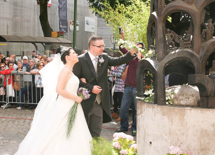 The couple at the foot of the Statue of St Anthony. The groom present a bouquet of flowers at the foot of the statue.