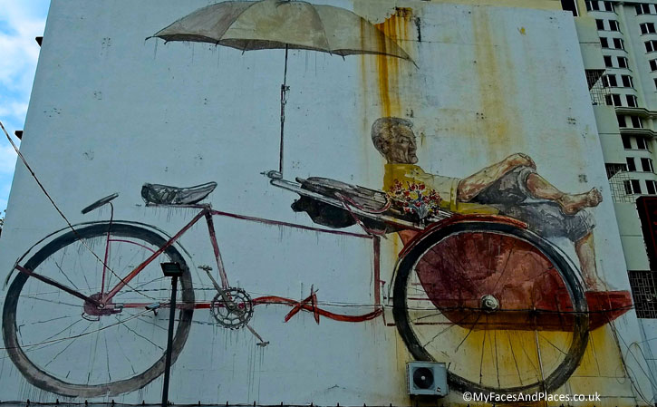 """""""The Awaiting Trishaw Peddler""""(Penang Road): An elderly trishaw peddler resting in his trishaw for customers. It is a fitting tribute to the trishaw peddlers who congregate at the trishaw station across the road, in front of the St Francis Xavier Church."""