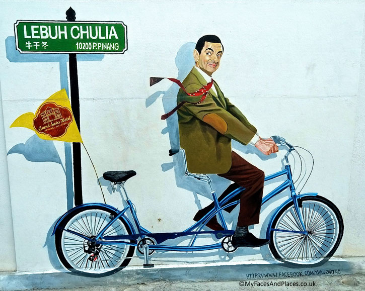 A mural of the famous Mr. Bean character on a bicycle on a wall along the alley to Grand Swiss Hotel in Chulia Street, George Town. This art work was done by Yakuzart Creation. It depicts an internationally recognisable personality in the property of an established Hotel Chain. This shows the recognition of Penang Street Art by the business community.