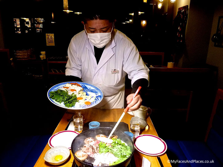 Our chef cooking the sukiyaki hot-pot at our table - autumn in Niseko