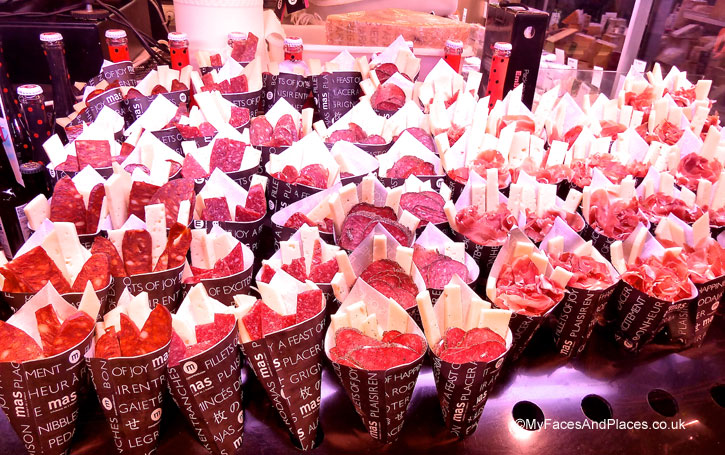 Lunchtime treat of ham and salami in paper cones at La Boqueria Market in Barcelona, Spain