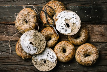 SESAME BAGELS SLATHERED WITH RICOTTA CHEESE & SESAME SEEDS LID ON RUSTIC WOODEN BOARD