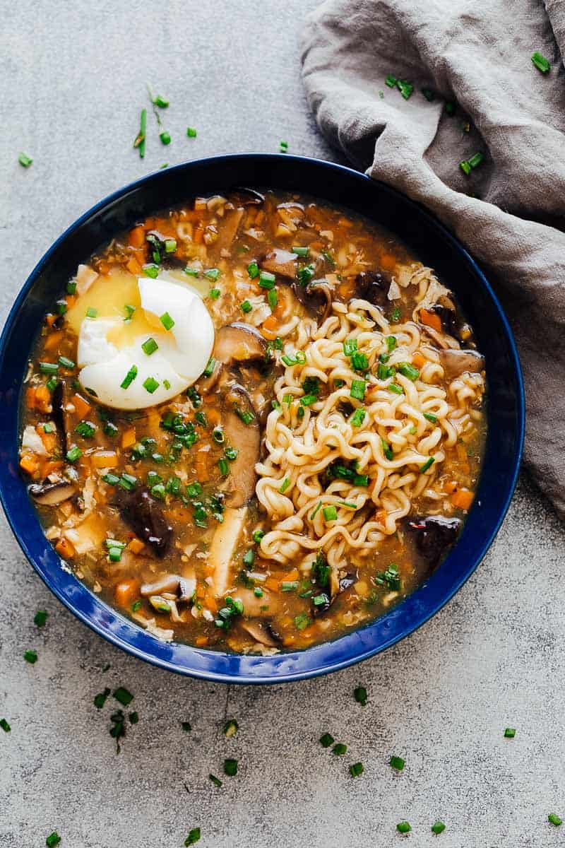 A bowl of chinese hot and sour soup with ramen served with a soft boiled egg and green onions ready to eat!