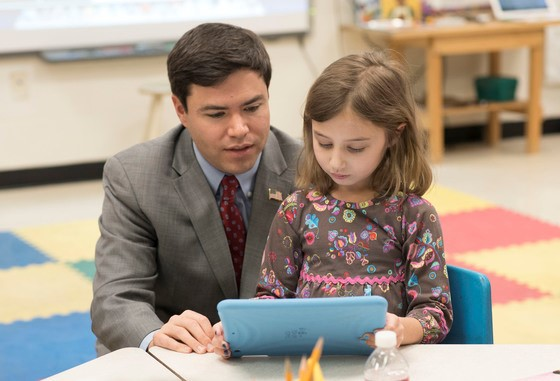 North Carolina Superintendent Mark Johnson looks at an iPad with a student. (North Carolina Department of Public Instruction)