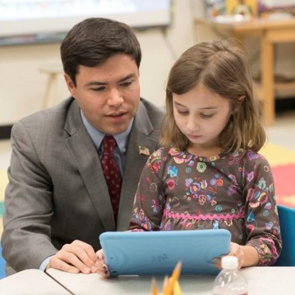 North Carolina Superintendent Mark Johnson looks at an iPad with a student. (North Carolina Department of Public Instruction)