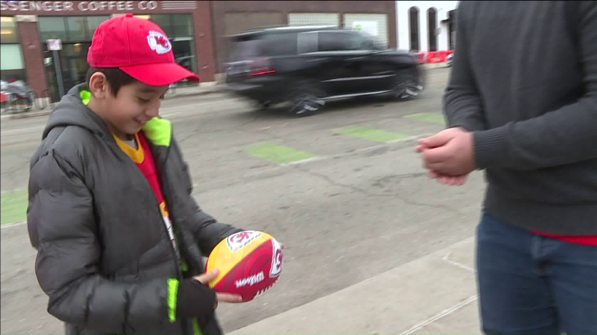 A boy is reunited with the Super Bowl souvenir ball he lost at the Chiefs parade. (Photo by WDAF)