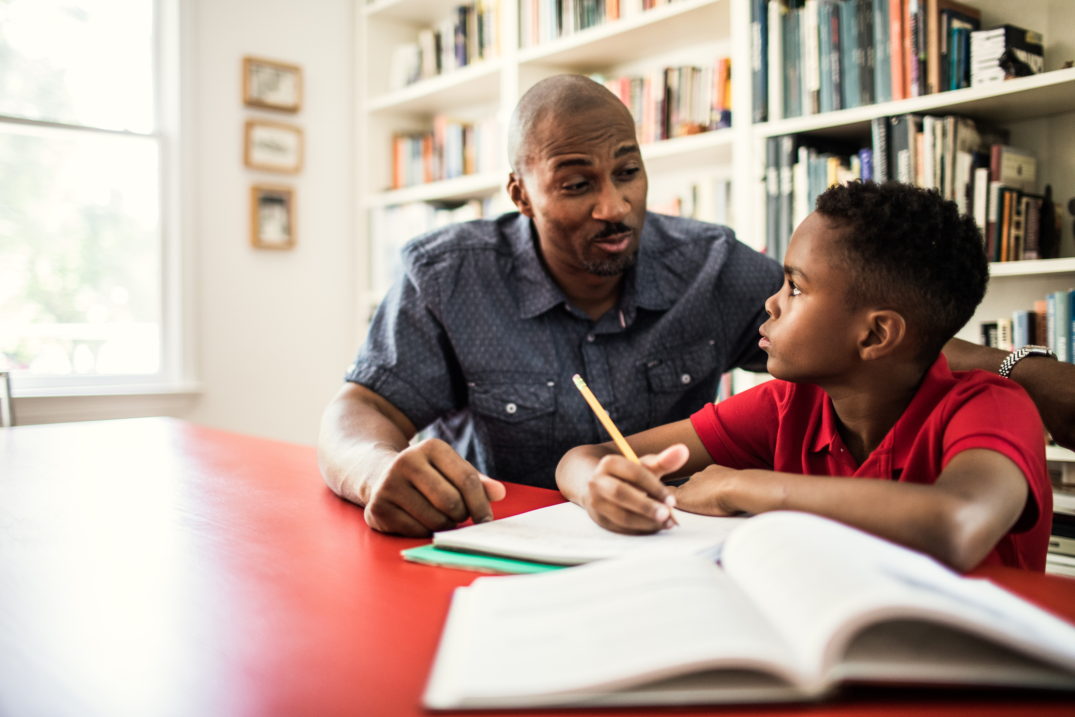 Stock image of father helping son with homework (Getty Images)