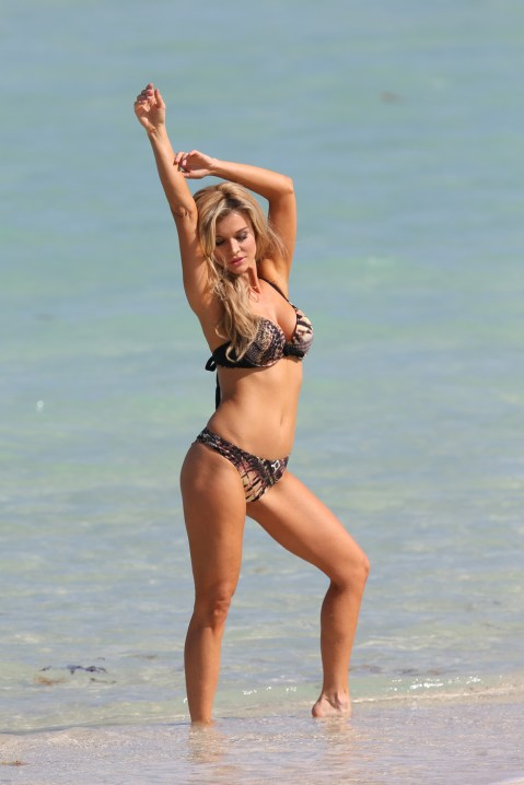 115832, Joanna Krupa shows off her incredible figure in an animal print bikini during a shoot for her 'Esotiq' swimwear line, on the beach in Miami. The Polish 'Real housewives of Miami' star posed up a storm during her photo shoot for the European lingerie and swimwear brand. After the shoot finished, the Polish beauty got dressed into a black and white striped dress before taking a selfie with a member of the crew. Miami, Florida - Tuesday April 01, 2014. Photograph: Brett Kaffee/Thibault Monnier © Pacific Coast News. Los Angeles Office: +1 310.822.0419 London Office: +44 208.090.4079 sales@pacificcoastnews.com FEE MUST BE AGREED PRIOR TO USAGE