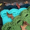 upclose picture of stack of Arcade Scallop Cowls in green, light teal, dark teal and black
