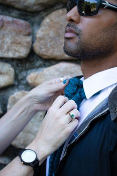 Man show in close up of his chest.  A woman's hands are shown adjusting the knitted necktie he's wearing