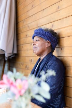 Woman sits with her back against a wood planked wall. She is smiling off into the distance and wearing a blue Marilue Cowl folded over as an ear warmer.