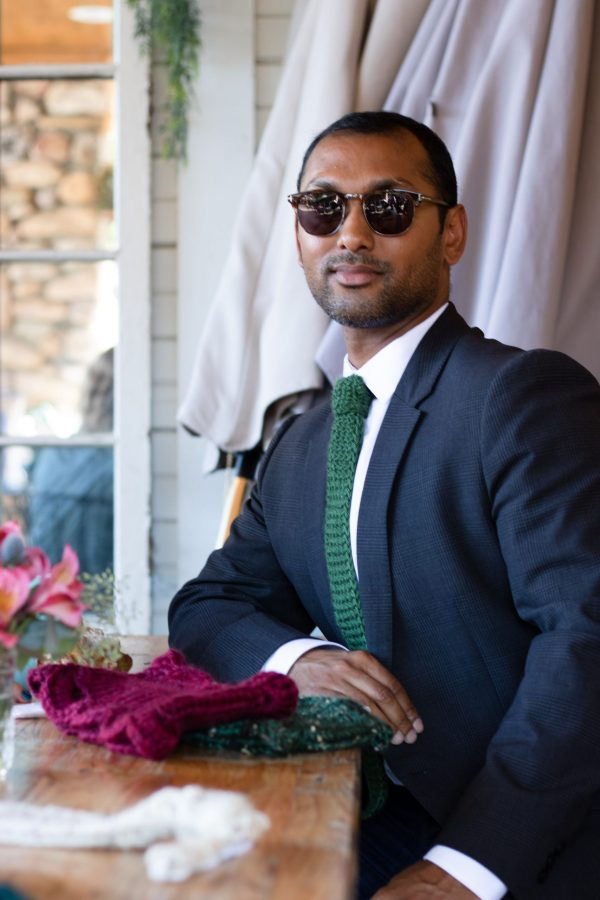 A man sits at a coffee shot. He's wearing sunglasses, a navy blazer and white shirt. He's styled his outfit with green knitted necktie.