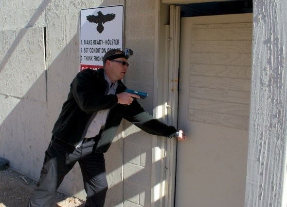 Step 1 of the house clearing exercise - opening the door. The Glock is equipped with a Simunitions conversion and the new LaserMax Native Green laser.