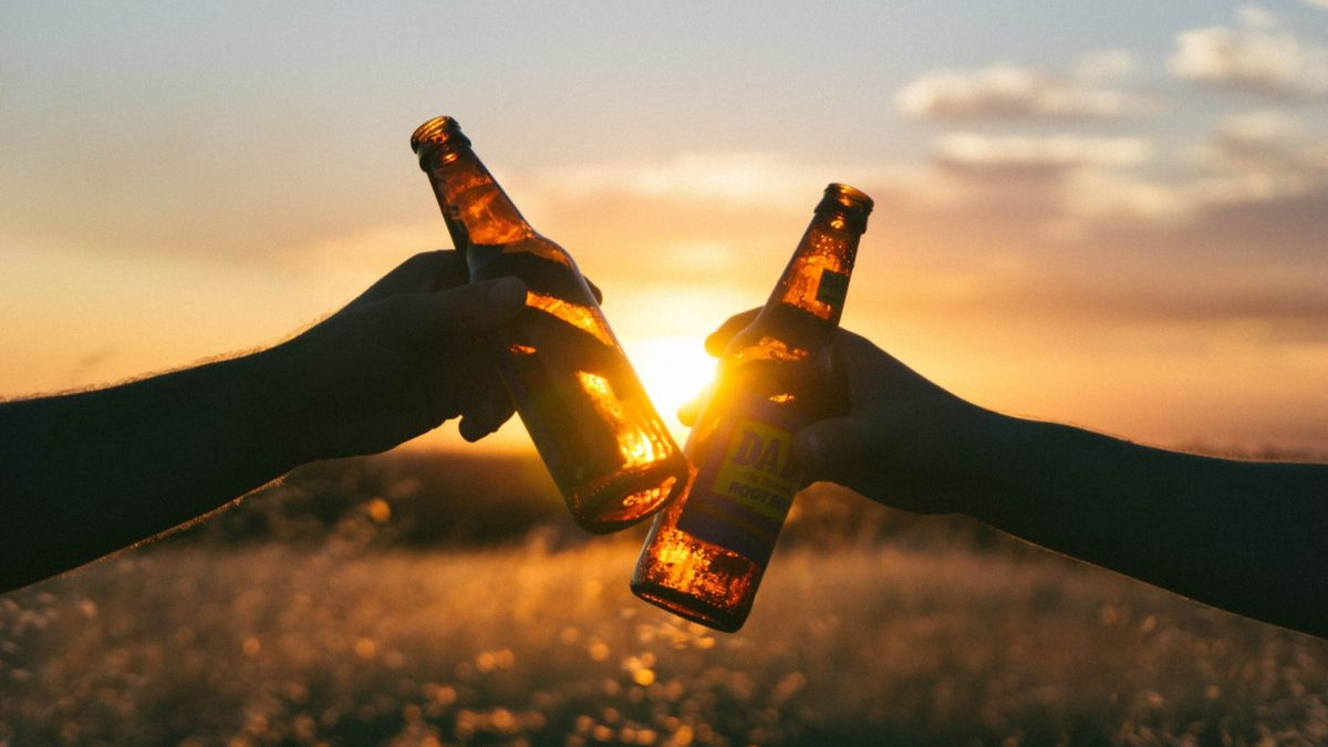 two beer bottles clanking in front of sunset