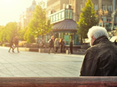 an elderly guy with gray hair sitting in the town square.