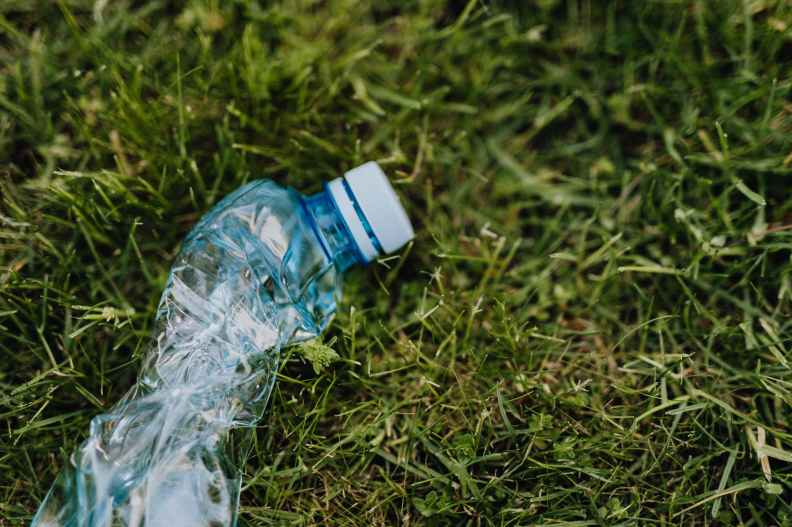 crushed plastic bottle on green park grass