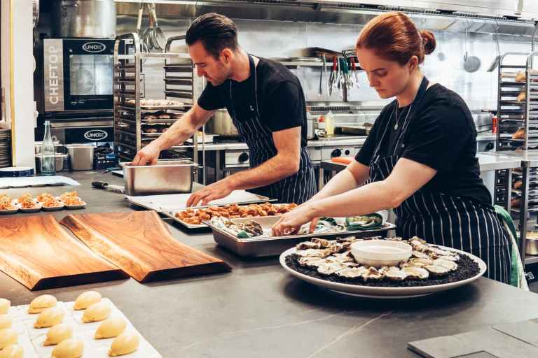 man and woman wearing black and white striped aprons