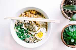 asian soup with boiled egg and green onions in bowl