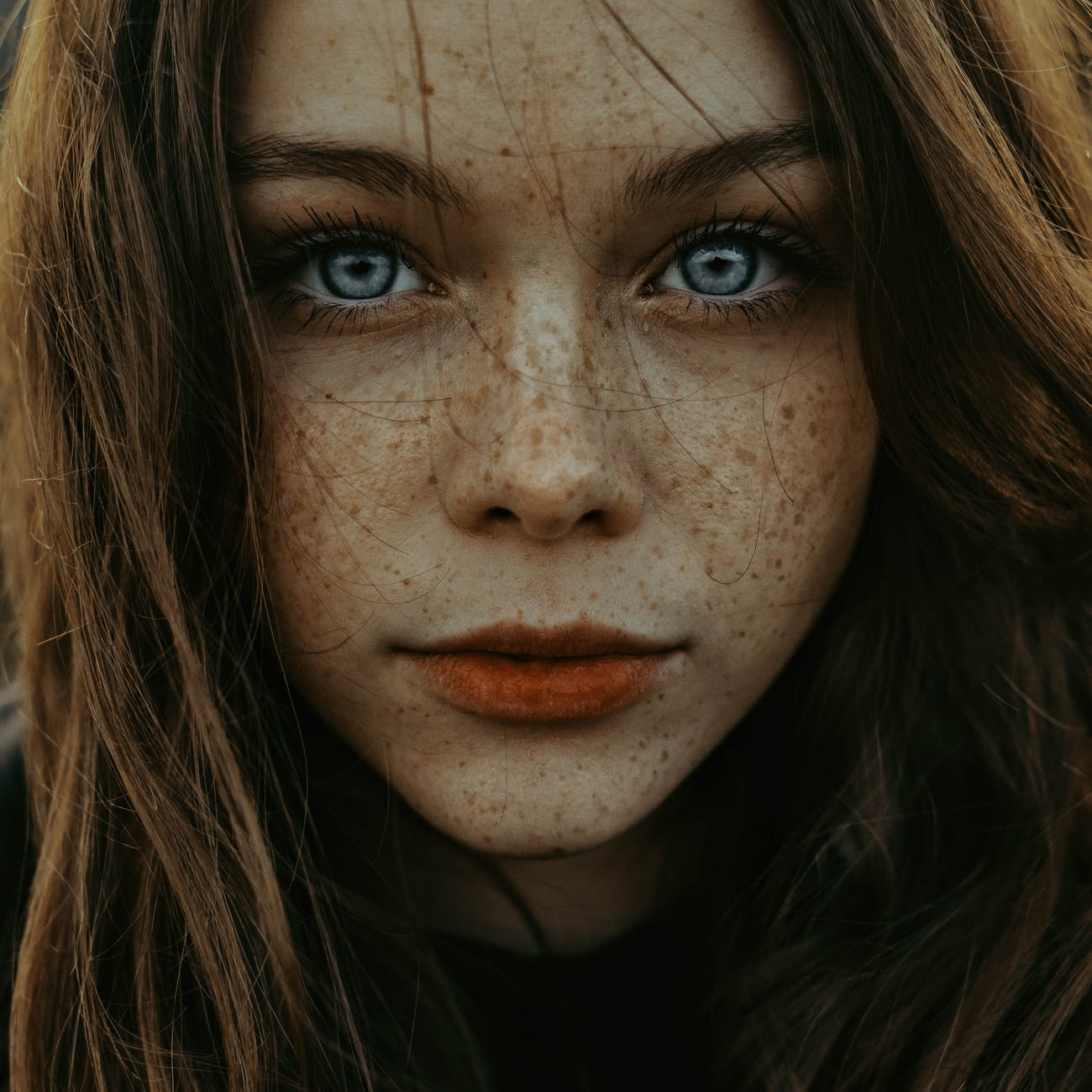 unemotional woman with freckles and big blue eyes