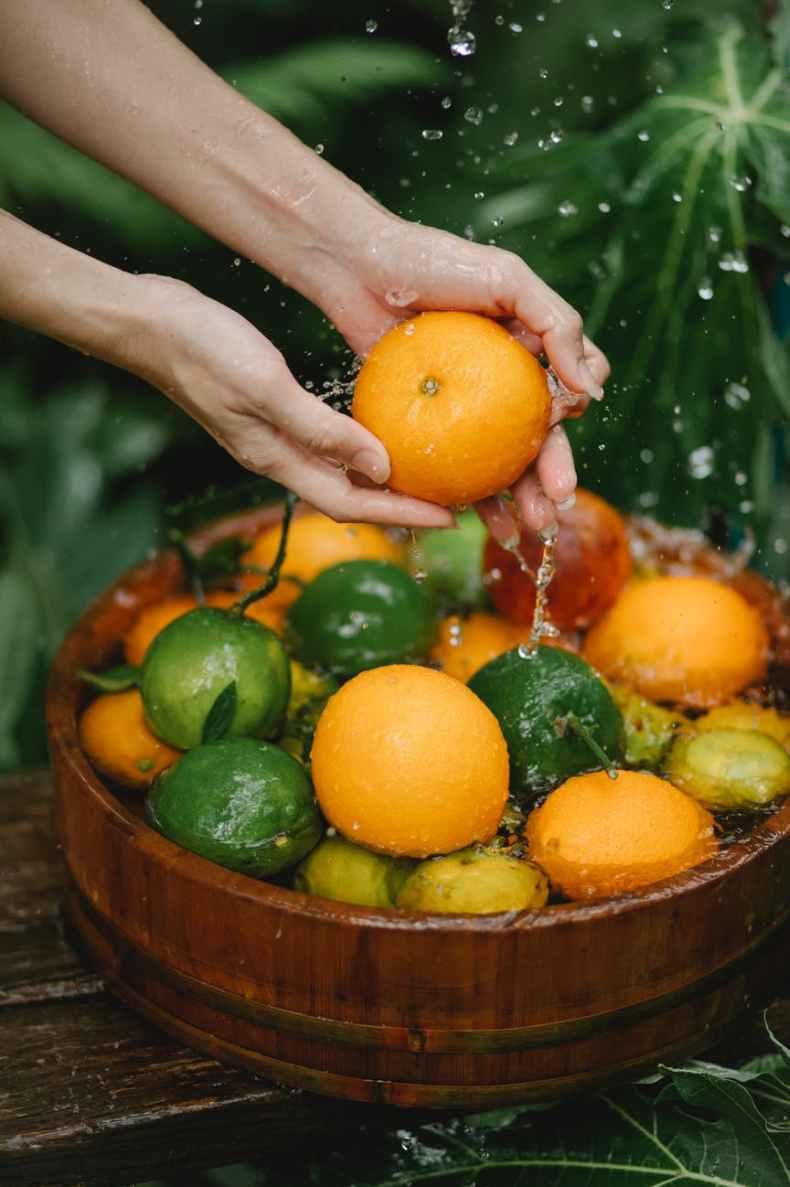 crop woman washing fresh fruits in bowl
