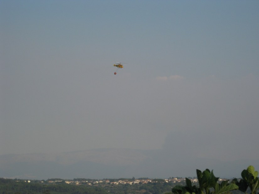 A helicopter carrying a bambi bucket of water to put out the fires