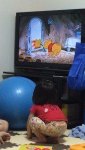 テレビでくまのプーさんの真似して両腕を地面に付ける幼児の後ろ姿