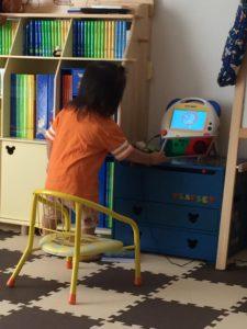 DVDメイトを見ながらマジックスクリーンで棚を叩く幼児の後ろ姿