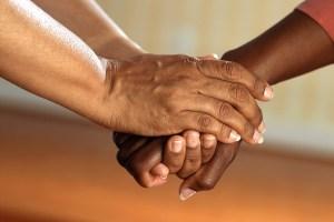 二人が握手してる手と腕のアップ