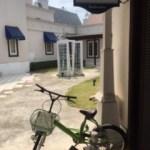 白い建物の手前にある自転車と小さな塔