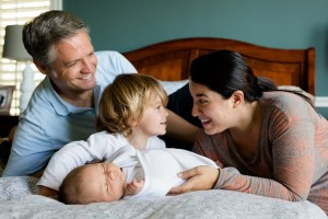 お父さんお母さんと幼児と赤ちゃんがベッドで戯れています