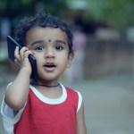 異国の少年が携帯電話に耳を当て良い表情で街中をたたずんでいます