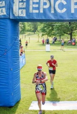 Hometown Bicycles' Amy Gluck crossing the finish line at Epic Races Island Lake Triceratops Triathlon