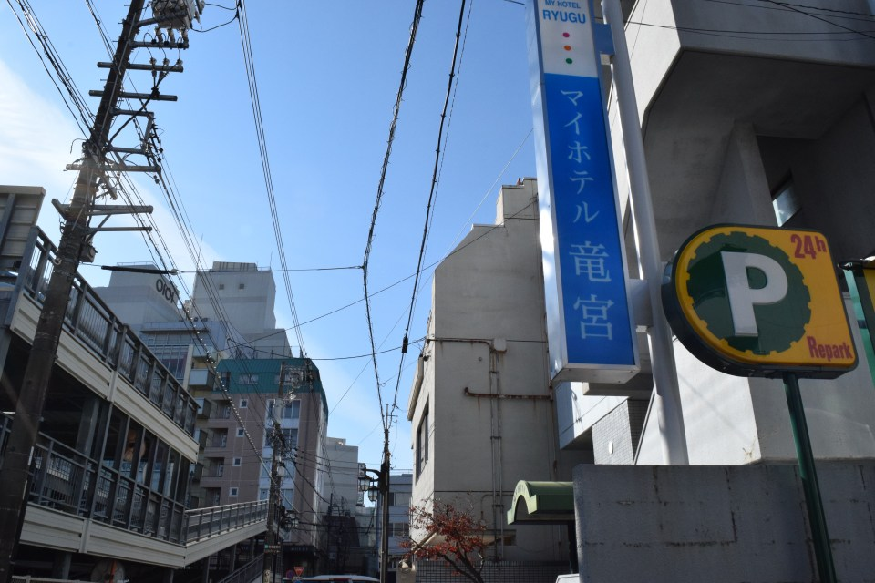 My Hotel Ryugu's back entrance- sign reading 'My Hotel Ryugu' in Japanese and a shizuoka street. マイホテル竜宮の裏口の看板と通り