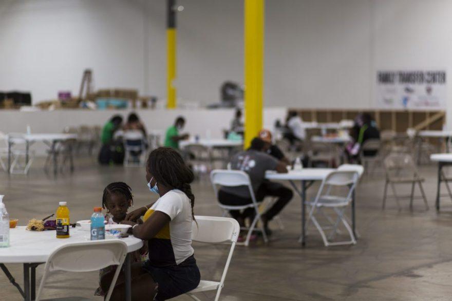 Two Haitian asylum seekers enjoy a meal at the NACC shelter. Photo b Leonardo March