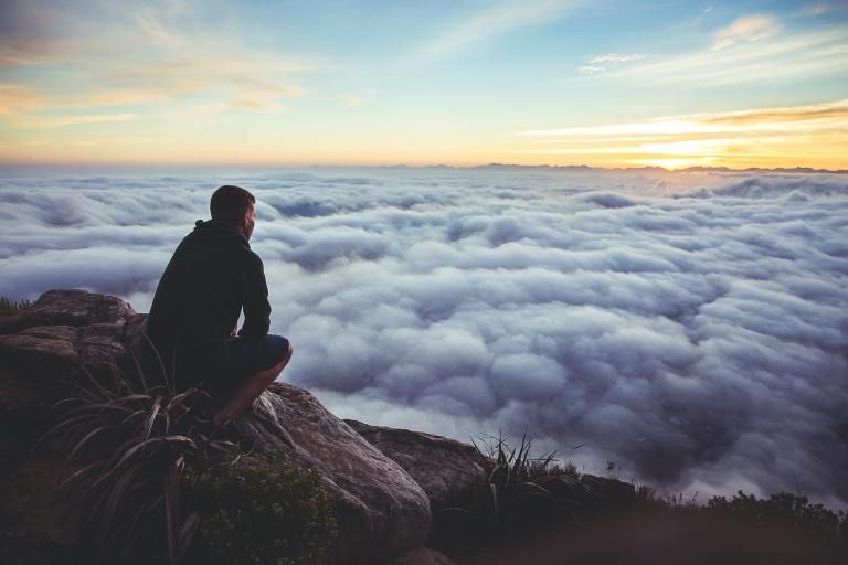 man looking over clouds from mountaintop