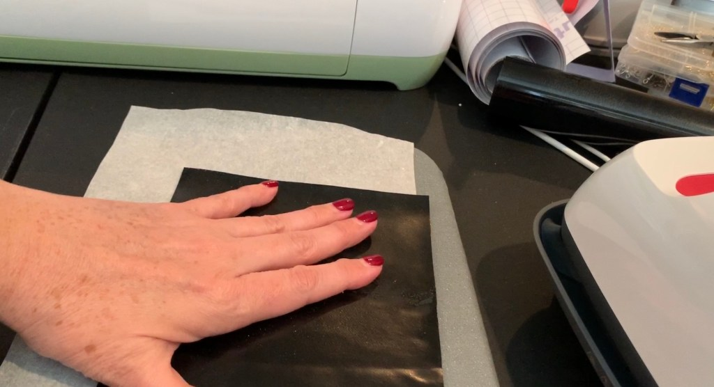 iron everyday heat transfer material onto the back of a cork sheet with a Cricut Easy Press